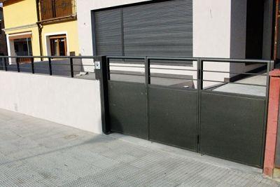 Puerta metálica con cercado para vivienda unifamiliar