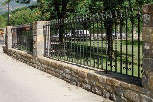 Muro de piedra con reja de forja integrada